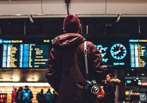 study-abroad-student-in-beanie-looking-at-flight-schedule-in-oslo-norway.jpg