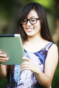 Girl Smiling at Her Tablet