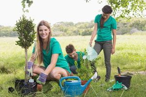 young adults volunteering and planting trees outside