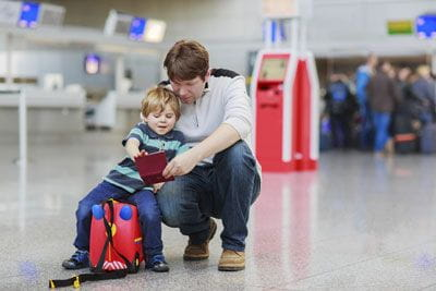 father and son with passport in airport