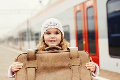 little girl with suitcase by train