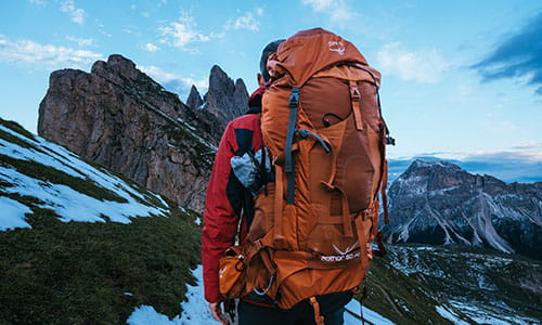 man-carrying-a-backpack-standing-on-a-mountain-in-italy.jpg