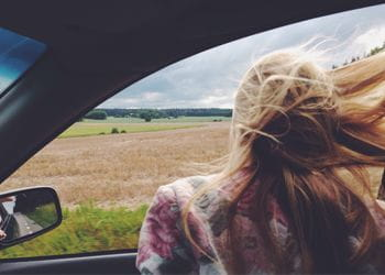 woman enjoying road trip with windows down