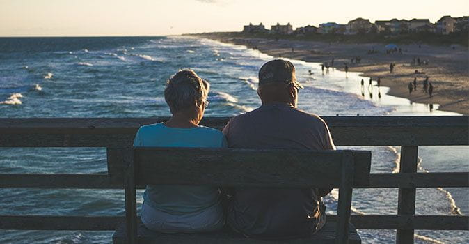 seniors-sitting-on-a-bench-by-the-ocean-outside-the-us